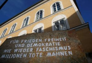 "The imposing htree story yellow house where Hitler was born has an engraved stone marker out front that reads: ""For peace, freedom, and democracy, never again fascism, millions of dead are a warning."""